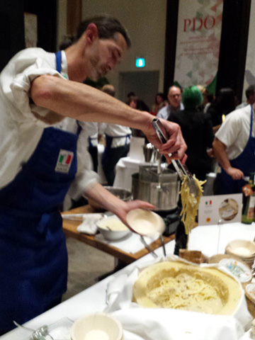 a chef serving pasta in a busy room