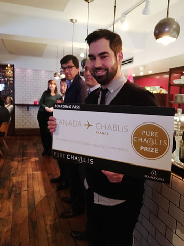 he's holding a big 'boarding pass' for a Canada-Chablis flight; it's labelled PURE CHABILS PRIZE