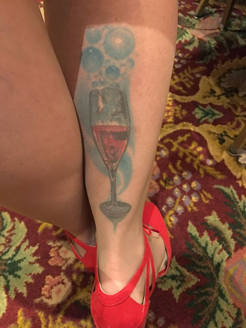 It's a champagne flute filled with rosé champagne on a swirly bubbly blue background, covering the lower half of the back of her right calf