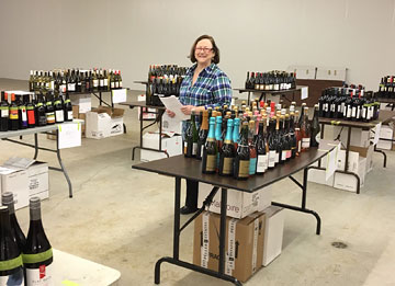 a woman standing in a large room surrounded by portable tables each of which has dozens of bottles of wine on it