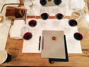 6 wine glasses, each containing 1 ounce of red wine, in a semicircle around a closed menu