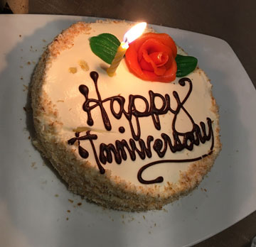 cake with Happy Anniversary on it,  with an icing rose and a single candle