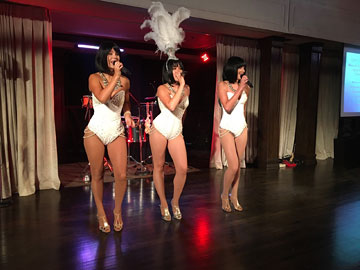 Three ladies in sequined white one-pieces singing on a stage; the one in the middle has a large white plume headpiece