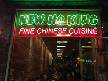 restaurant window with NEW HO KING FINE CHINESE CUISINE neon sign in the window and diners behind