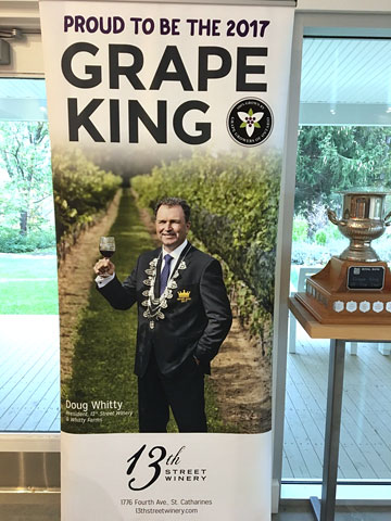 standing display banner with picture and text: PROUD TO BE THE 2017 GRAPE KING [picture] Doug Whitty, 13th Street Winery